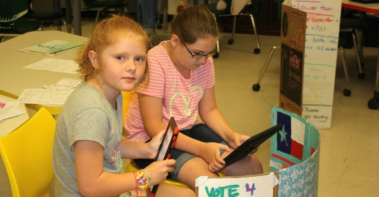 Two longview girl students work on poster project