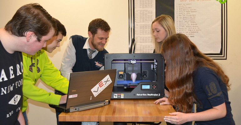 Teacher instructs students on using 3D printer